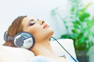 Portrait of resting young woman at home with listening music. Closed eyes.